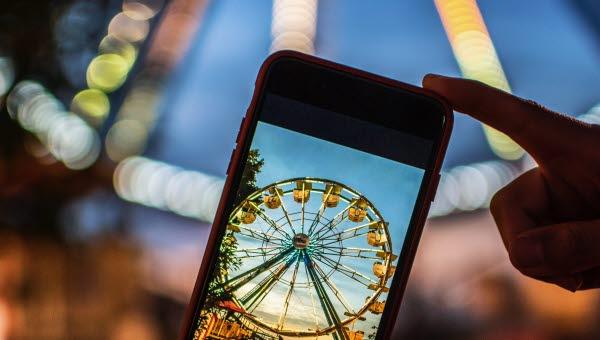 Metabild: Person tar en bild på ett Pariserhjul med mobilen och ser motivet både i mobilen och i verkligheten