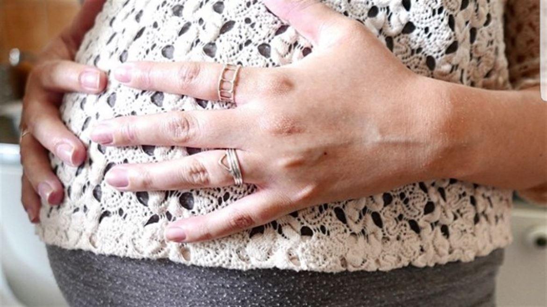Gravid kvinna med händerna på magen