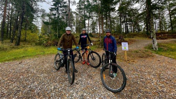Tre personer står med varsin cykel i skogen