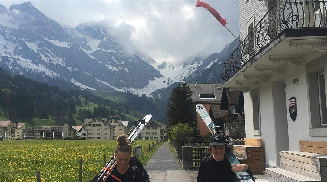 Alexandra och Andrea bär alpinskidor i Luzern
