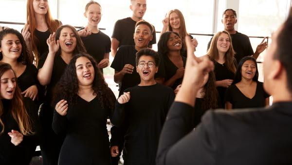 kvinnliga och manliga studneter sjunger i kör med körledare