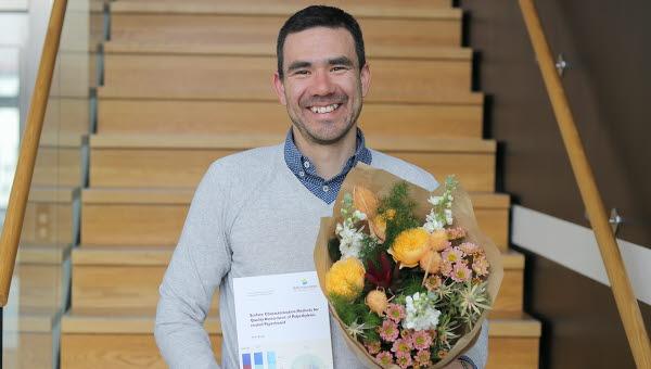Bild på nydisputerad Javier Brugés med blommor i handen
