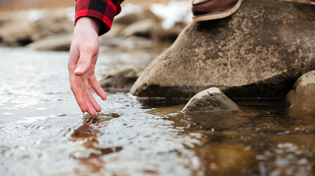 Vattendrag hand testar vatten