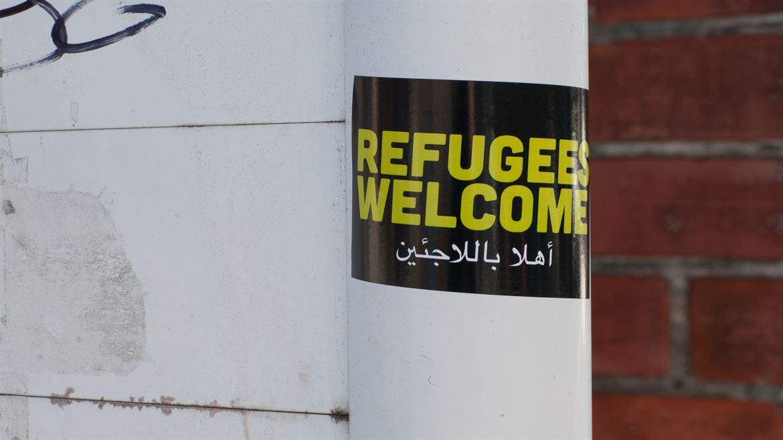 Klistermärke på stolpe Refugees welcome